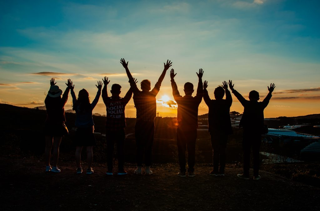 silhouette of people jumping at sunset with hands raised