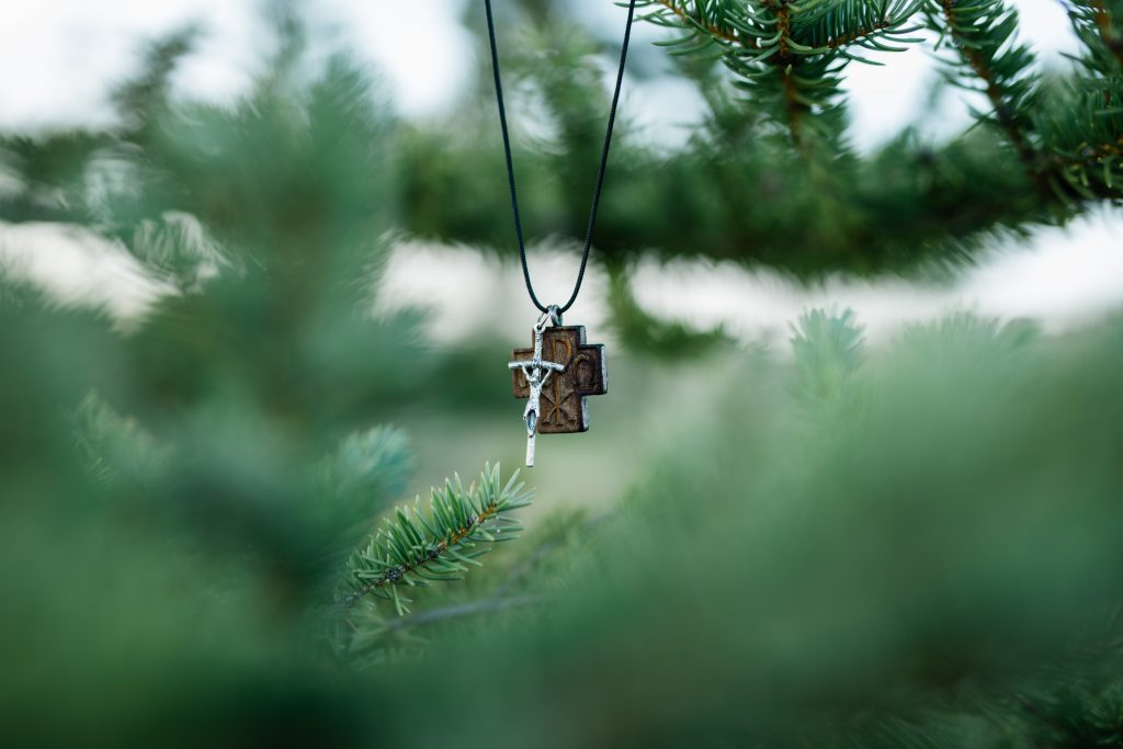 in a forest picture of a crucifix necklace