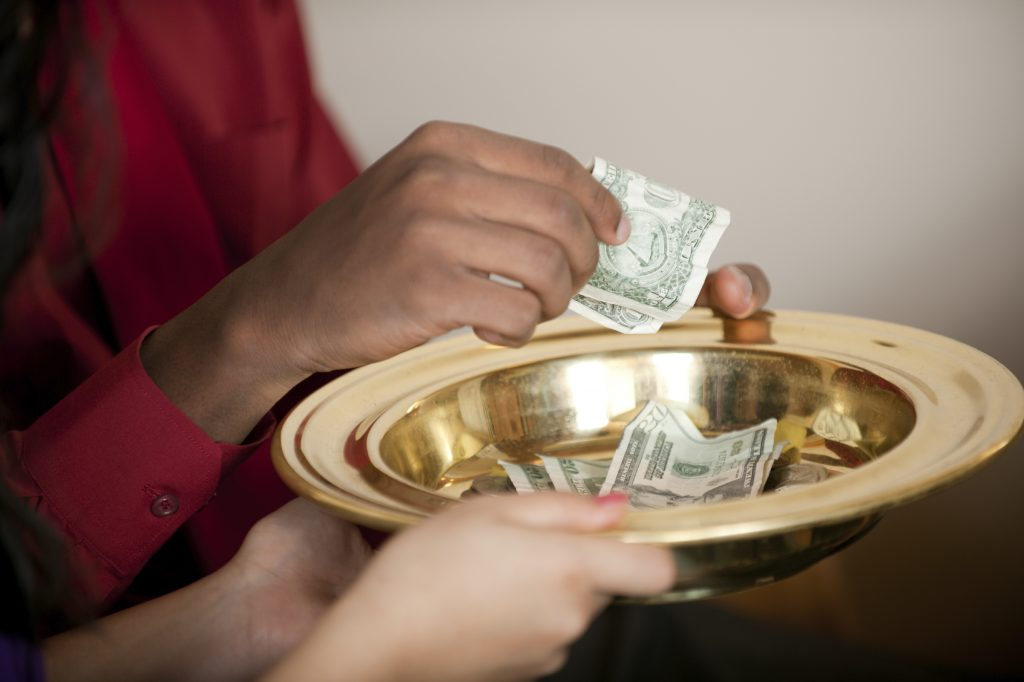 person dropping money in a collection plate